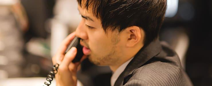 レンタルオフィスで電話対応する男性